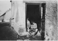 Brian Arbon at back door of terrace house with Robert behind