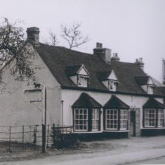 Coach & Horses sign advertising Collins Riding school. Brewery Wells & Winch 1958 note cycle shop to right | (Deacon)